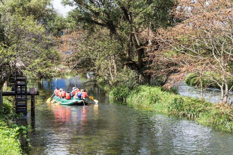 Grupp människor på flotten som langer på den fridfulla sceniska floden fotografering för bildbyråer