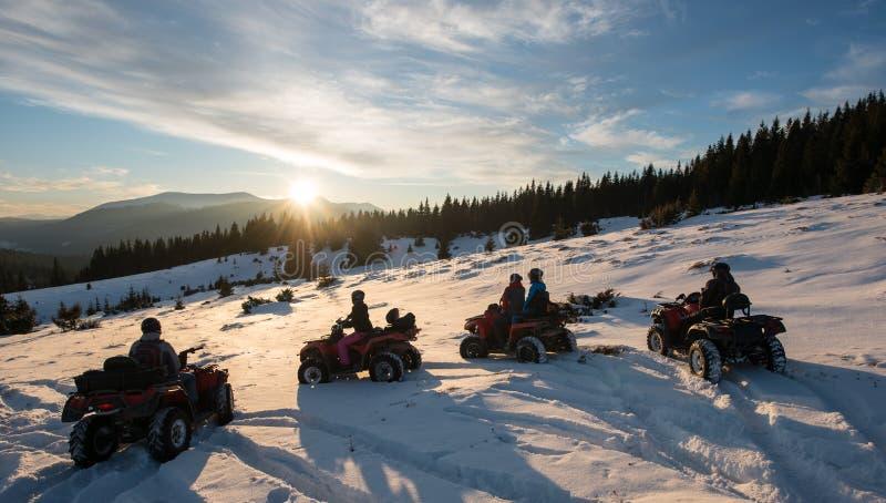 Grupp människor på fyrhjulingar ATV cyklar och att tycka om härlig solnedgång i bergen i vinter fotografering för bildbyråer