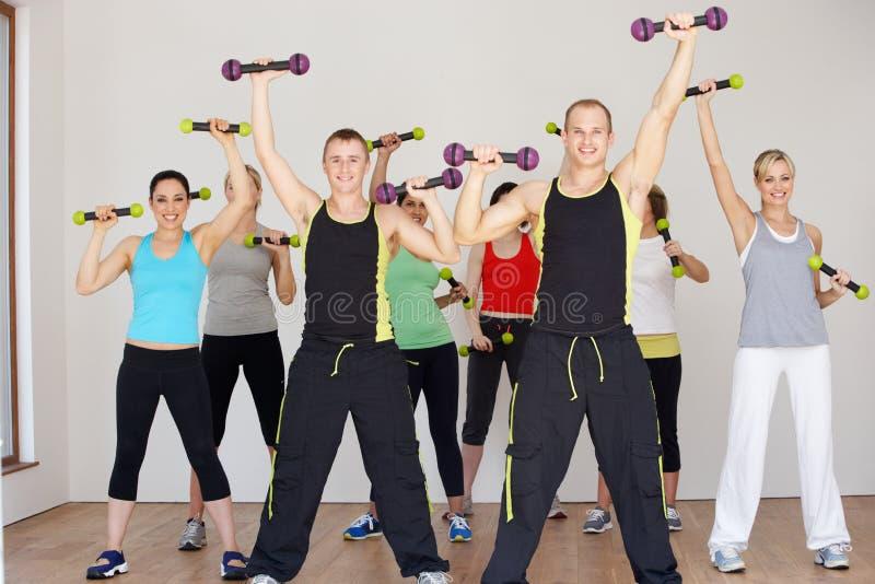Grupp människor som övar i dansstudio med vikter royaltyfri bild
