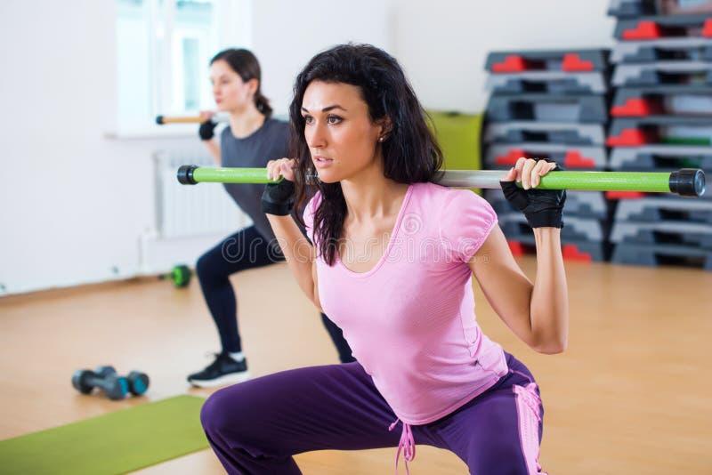 Grupp människor som excercising med stänger i idrottshallen som gör squatting en skivstång på konditionklubban arkivbilder