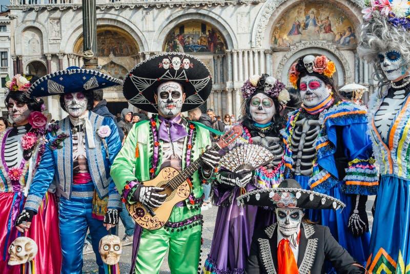 Grupp människor som förställas som skelett under den Venetian karnevalet arkivfoto