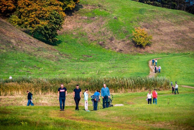 Grupp människor som går nära Kernave kullar royaltyfri bild