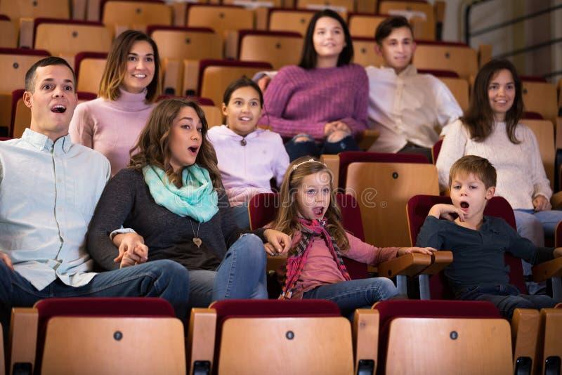Grupp människor som håller ögonen på spännande film royaltyfria foton