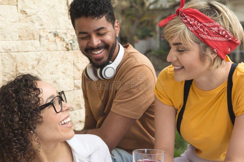 Grupp människor som har gyckel tillsammans på den utomhus- kaféstången Vår, arkivbilder