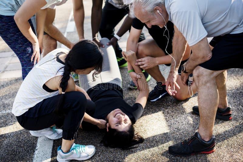 Grupp människor som hjälper en sårad person arkivfoto