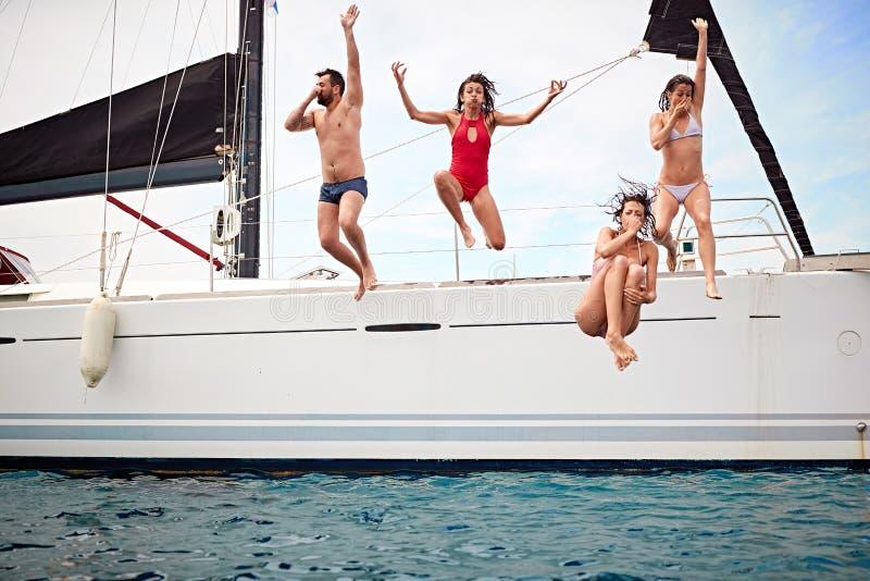 Grupp människor som hoppar i vattnet under ett fartyg royaltyfria bilder