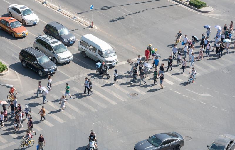 Grupp människor som korsar en hög trafikaveny i Peking, Kina arkivfoto