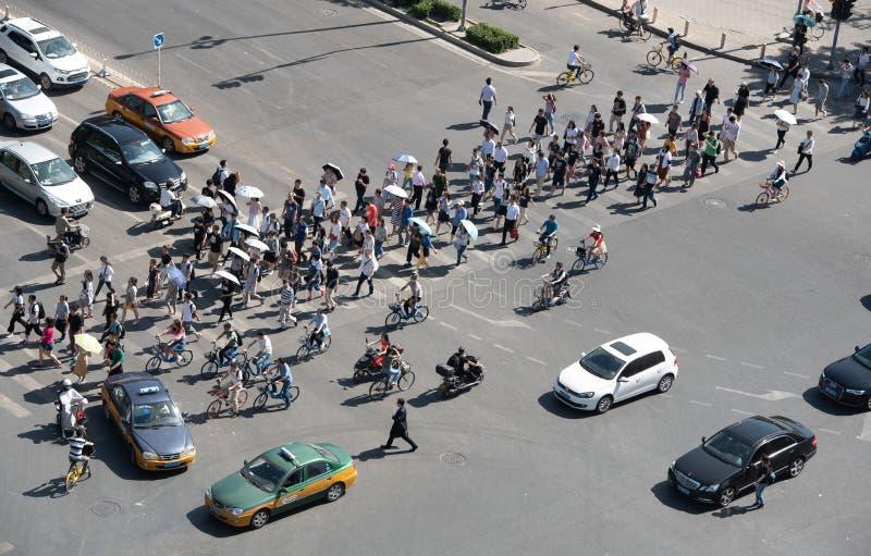 Grupp människor som korsar en hög trafikaveny i staden av, är royaltyfri foto
