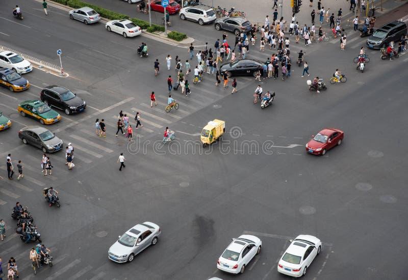 Grupp människor som korsar en hög trafikaveny i staden av, är arkivfoto