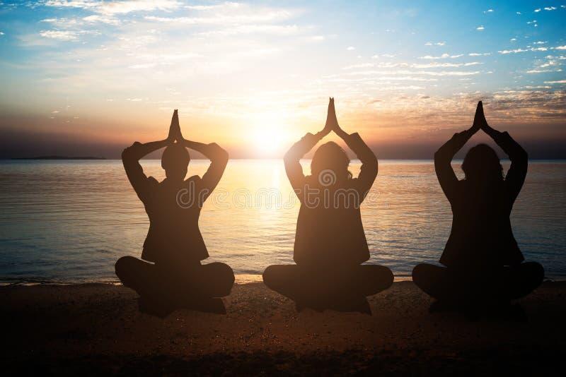 Grupp m?nniskor som mediterar p? stranden arkivfoton