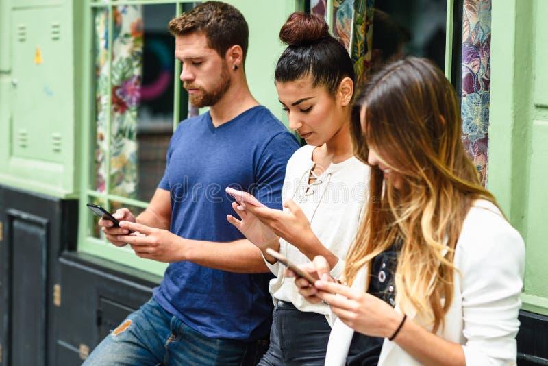 Grupp människor som ner ser på den smarta telefonen, begrepp om teknologiböjelse och ungdom arkivbild
