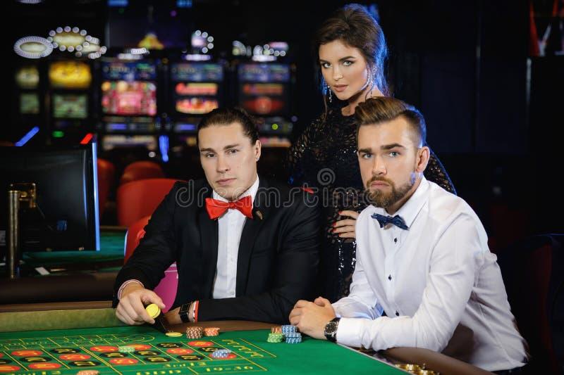 Grupp människor som spelar rouletten i kasinot royaltyfri fotografi