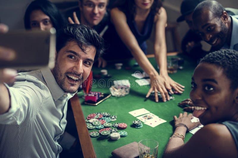 Grupp människor som spelar vågspel i kasino och tar selfie royaltyfri foto