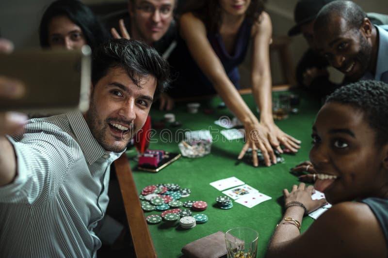 Grupp människor som spelar vågspel i kasino och tar selfie royaltyfri fotografi