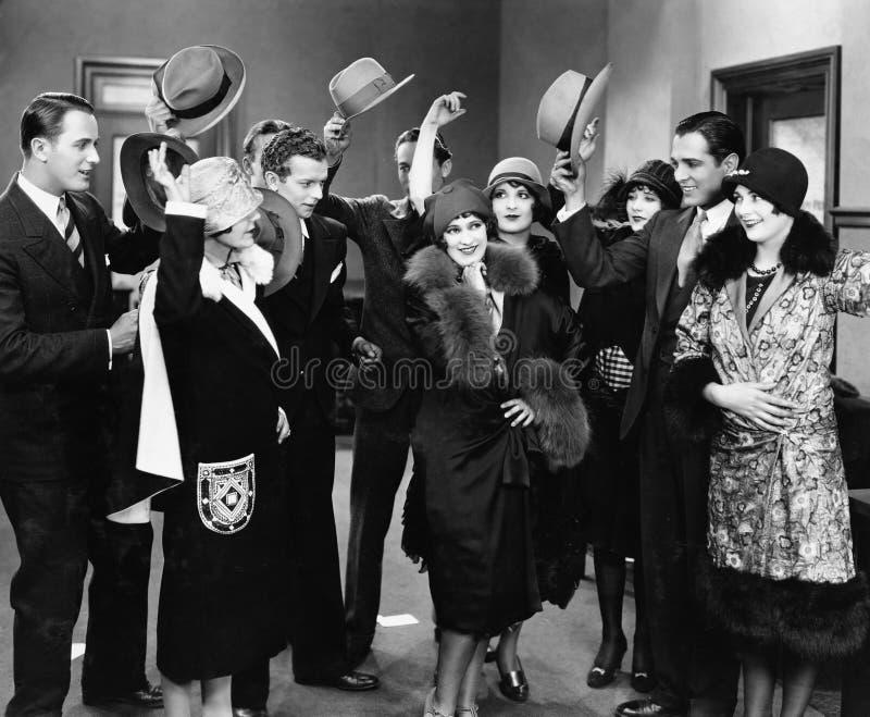 Grupp människor som tar av hattar till kvinnan (alla visade personer inte är längre uppehälle, och inget gods finns Leverantörgar arkivbilder