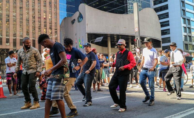 Grupp människor som tillsammans dansar på gatan arkivbild