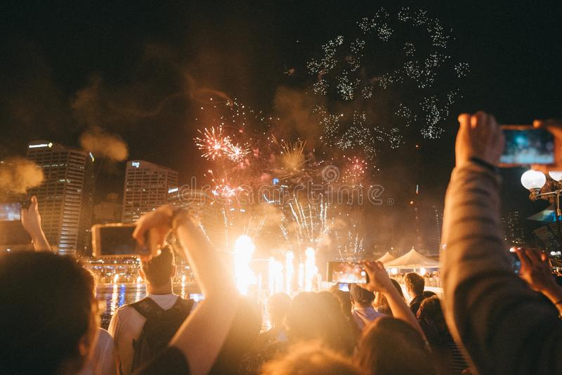 Grupp människor som tycker om ljusa gristrande fyrverkerier på en festival royaltyfria bilder