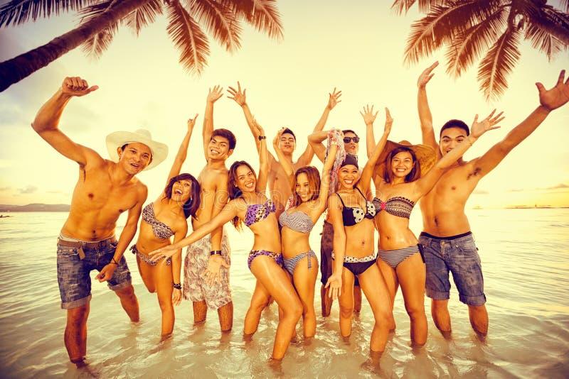 Grupp människor som tycker om på strandpartiet royaltyfri fotografi