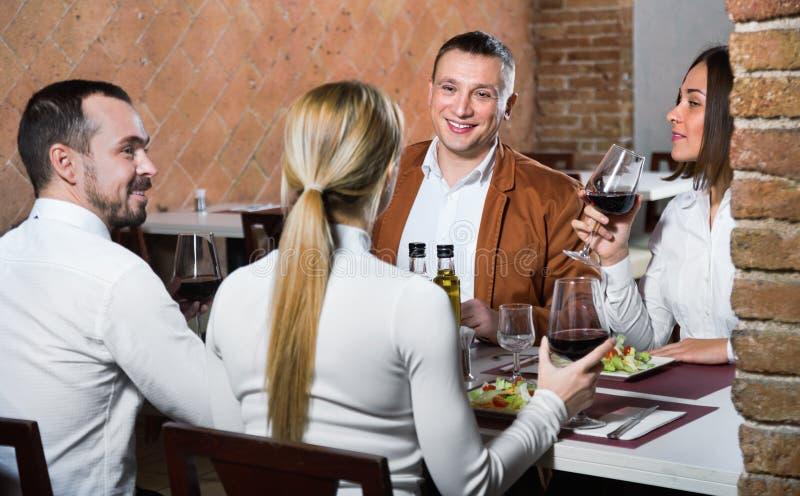Grupp människor som ut glatt äter middag i landsrestaurang arkivfoto