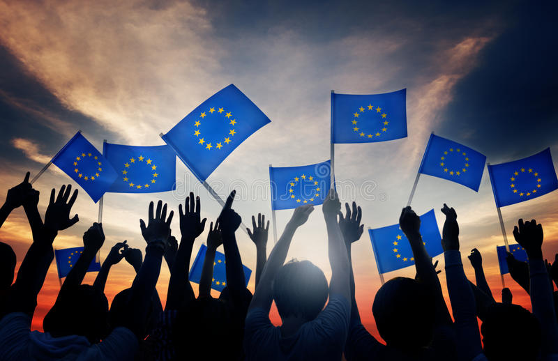 Grupp människor som vinkar europeiska fackliga flaggor royaltyfri foto
