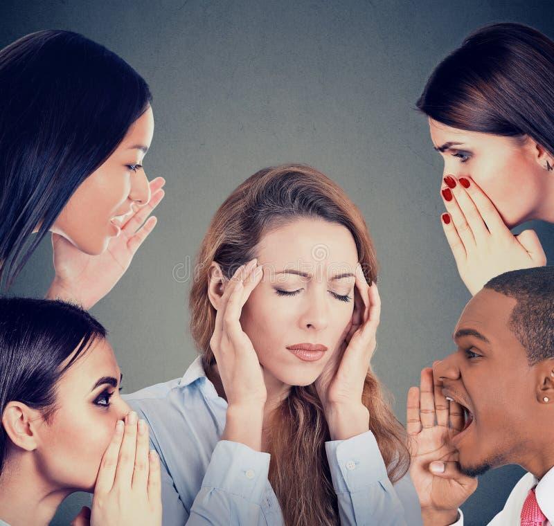 Grupp människor som viskar skvaller till ett stressat kvinnalidande från huvudvärk arkivfoton