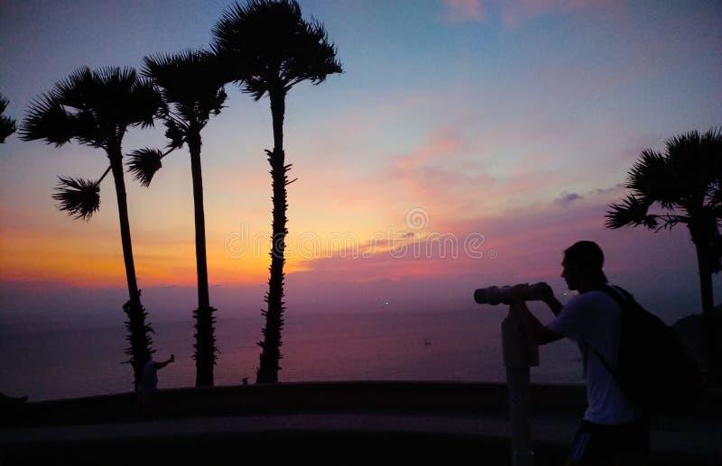 Grupp människor tar fotoet på stranden på solnedgång arkivbild