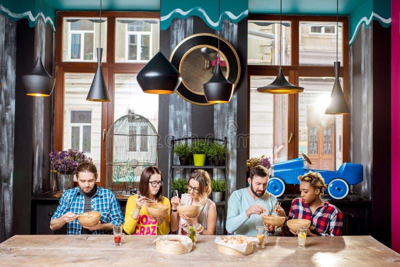 Grupp människor under matställen på den asiatiska matrestaurangen royaltyfri bild