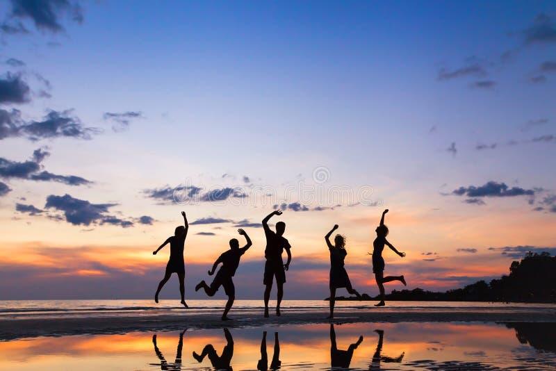 Grupp människorbanhoppning på stranden på solnedgången royaltyfri bild