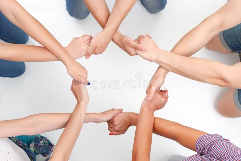 Grupp människordanandecirkel med händer arkivbilder