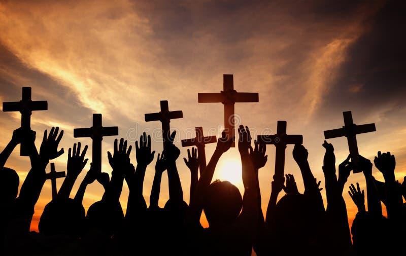 Grupp människorinnehavkors och be i tillbaka Lit arkivfoto