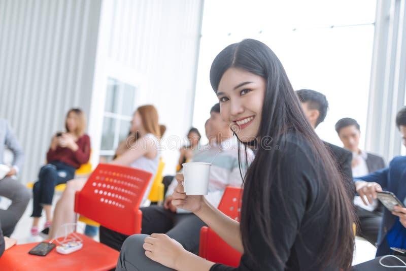 Grupp människorsammanträde och väntande på möte Asiatisk kvinna som rymmer kaffekoppen arkivbild