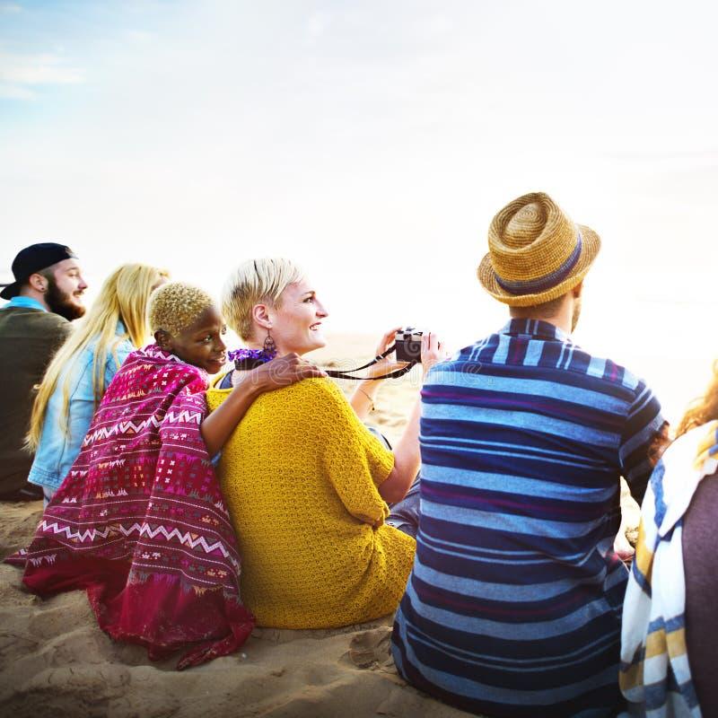 Grupp människorsammanträde på strandbegreppet arkivbild