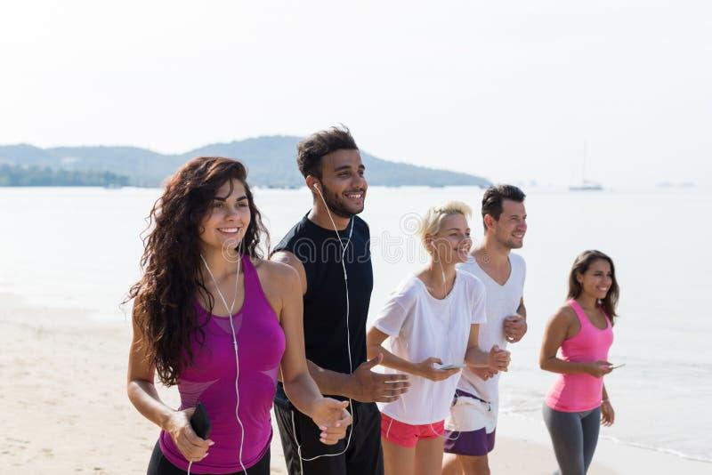 Grupp människorspring, ungt lopp för sportlöpareblandning som joggar på stranden som utarbetar le den lyckliga färdiga mannen och royaltyfria foton