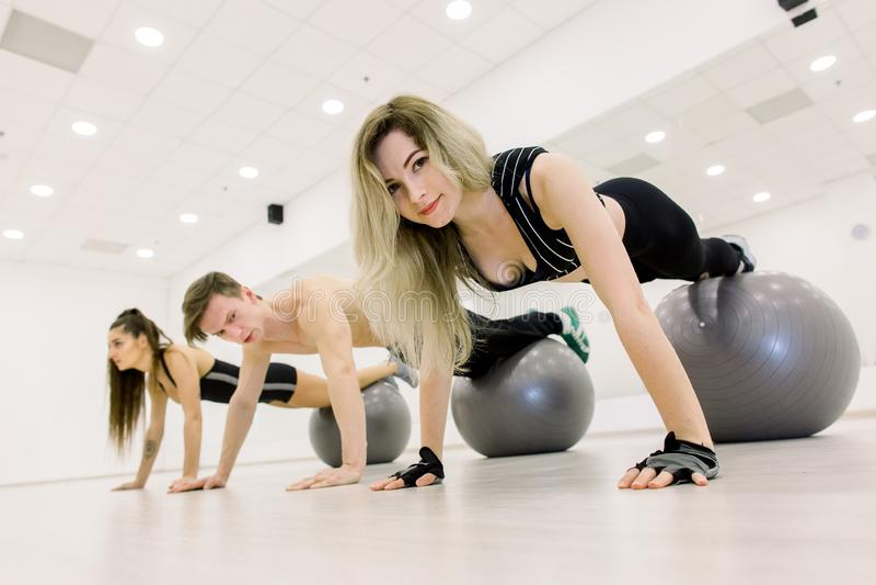 Grupp m?nniskorutbildning med fitballs i idrottshall Tv? unga sportiga kvinnor och man som g?r plankan med ben p? fitball p? idro fotografering för bildbyråer