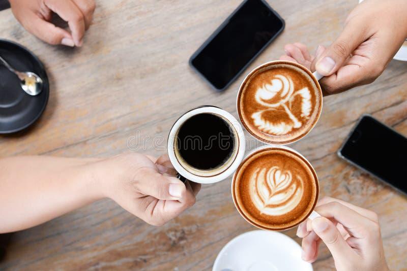 Grupp m?nniskor som har ett m?te efter lyckad aff?rsf?rhandling i en coffee shop Dricka varmt kaffe f?r drycklattekonst royaltyfria foton