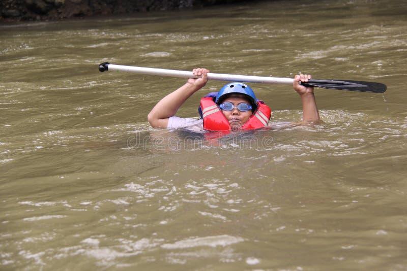 grupp m?nniskor som spelar rafting p? en flod, som har ett tungt fl?de, royaltyfri fotografi