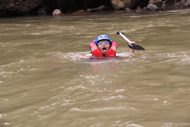 grupp m?nniskor som spelar rafting p? en flod, som har ett tungt fl?de, royaltyfri bild