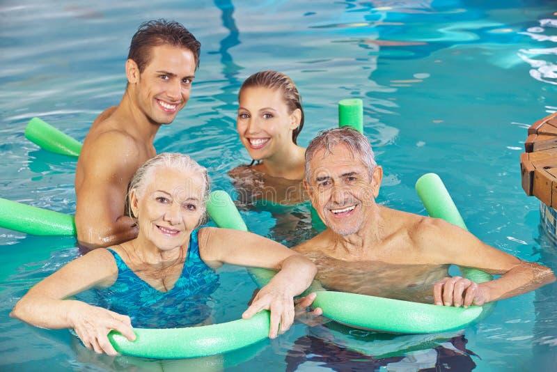 Grupp med par och pensionärer i simbassäng arkivfoto
