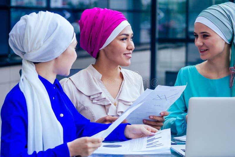 Grupp med tre kaukasiska muslimska kontorsdam som diskuterar med en affärskvinna och en intervju med arbetskamrater om sjö och tu royaltyfri foto