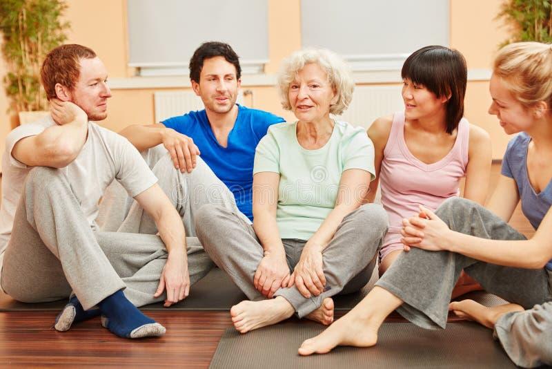 Grupp- och pensionärkvinna i yogagrupp royaltyfri bild
