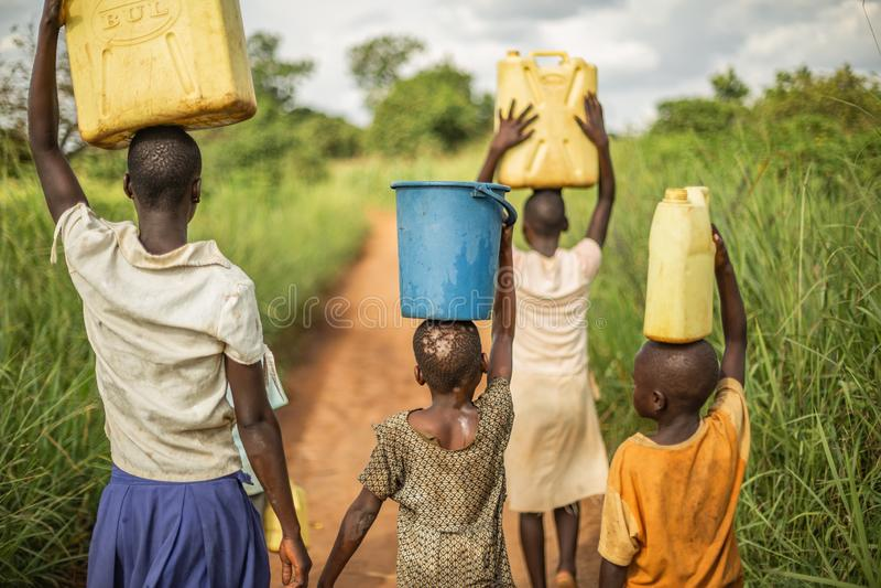 Grupp, om den unga afrikanen lurar att gå med hinkar och bensindunkar på deras huvud, som de förbereder sig att komma med rent va fotografering för bildbyråer