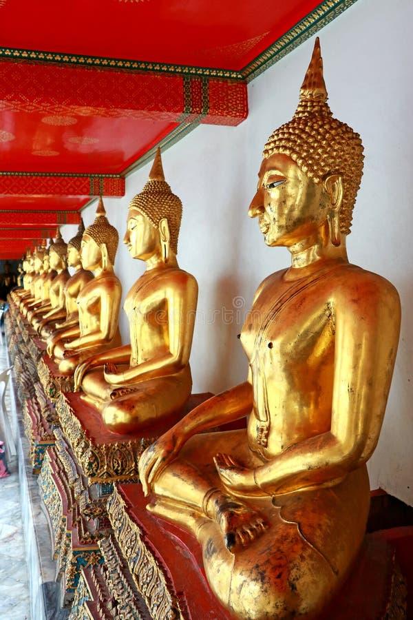 Gruppbilder av den guld- Buddhastatystuckaturen i olik ställing i lång korridor av Wat Phra Temple, Bangkok, Thailand royaltyfri foto