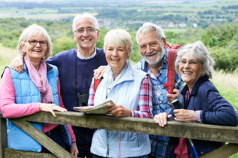 Gruppe ältere Freunde, die in der Landschaft wandern lizenzfreie stockbilder