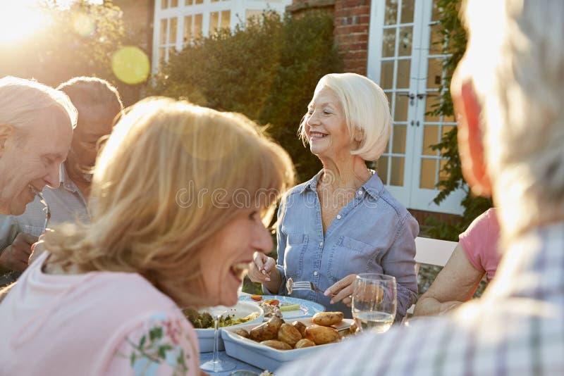 Gruppe ältere Freunde, die zu Hause Abendessen im Freien genießen stockbild