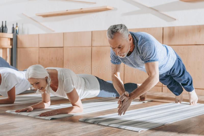 Gruppe ältere Leute, die Planke auf Yogamatten tun stockbilder