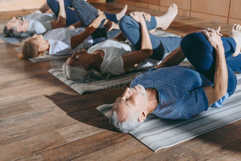Gruppe ältere Leute, die in Yogamatten ausdehnen lizenzfreies stockbild