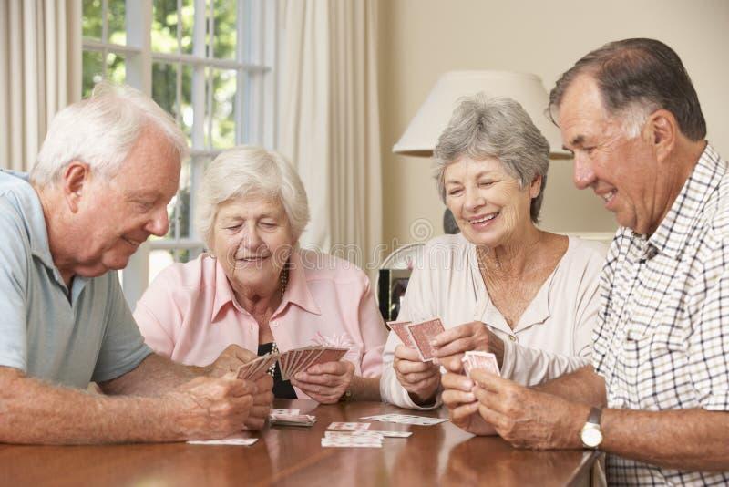 Gruppe ältere Paare Spiel von Karten zu Hause genießend stockfoto