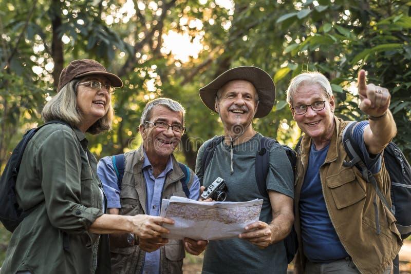 Gruppe ältere Trekkers, die eine Karte auf Richtung überprüfen stockfoto