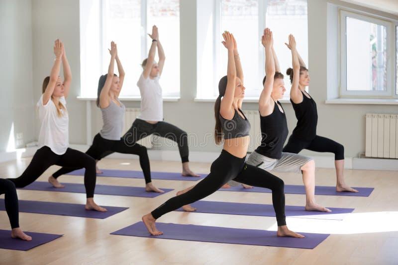 Gruppe übendes Yoga der sportlichen Leute, Haltung des Kriegers einer tuend lizenzfreie stockfotografie