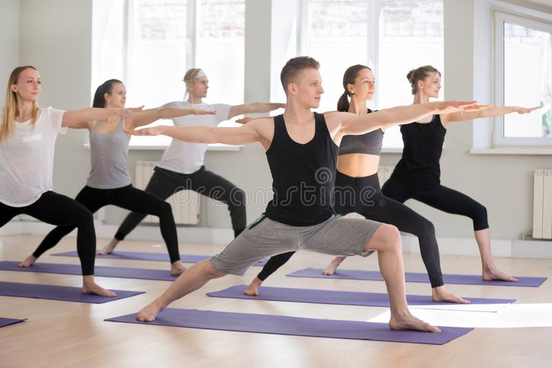 Gruppe übendes Yoga der sportlichen Leute, Haltung des Kriegers zwei tuend stockfotografie